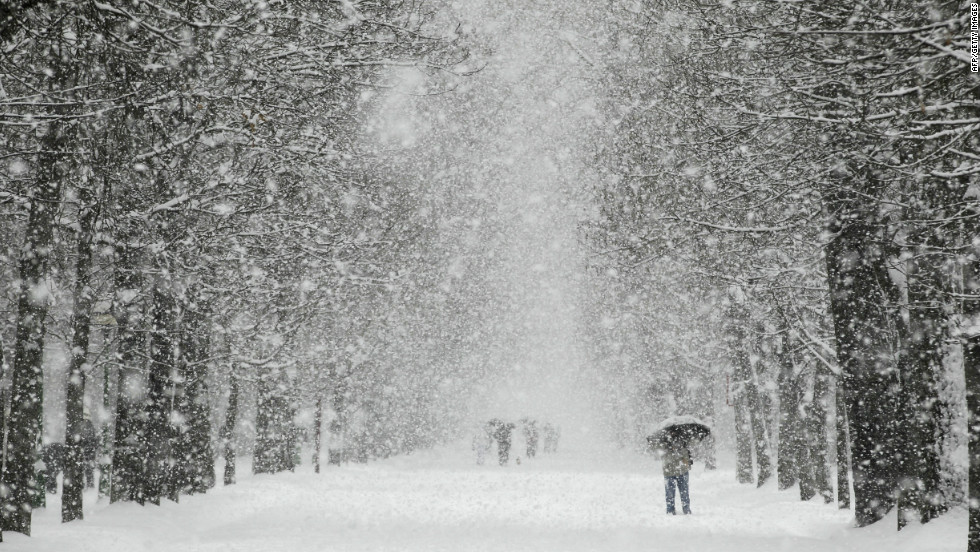 People walk through a park in Burgos as snow hits northern Spain on Sunday.
