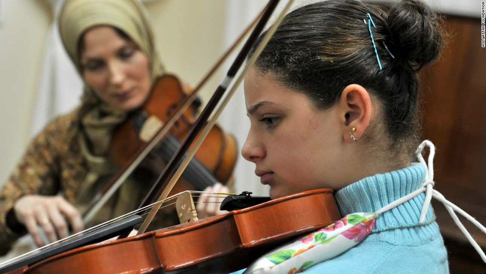 Violin teacher Elena Radwan playing with a student at Gaza Music School