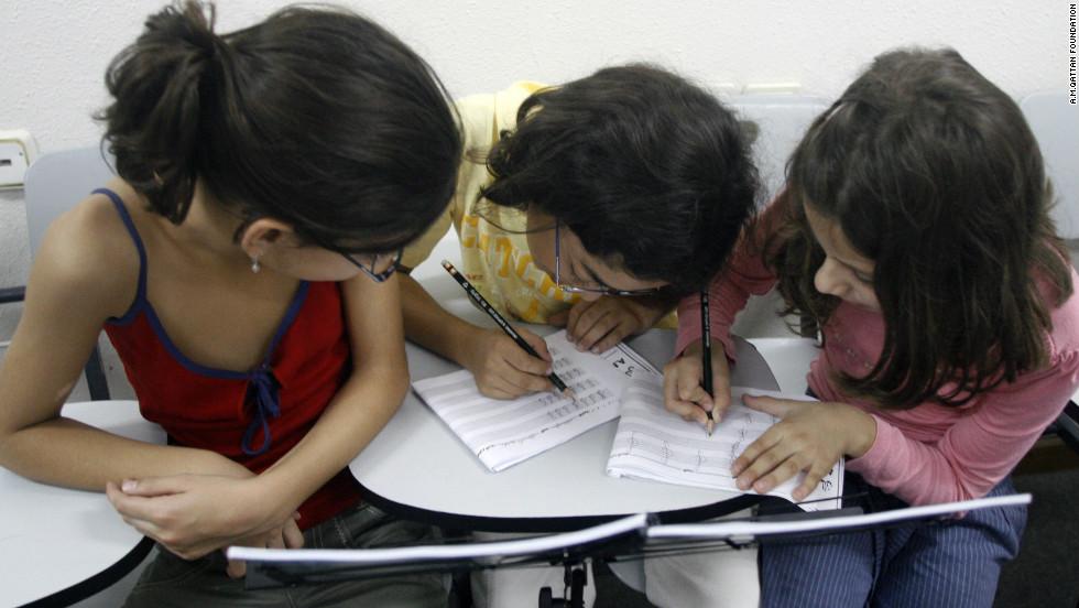 Three girls study musical notes