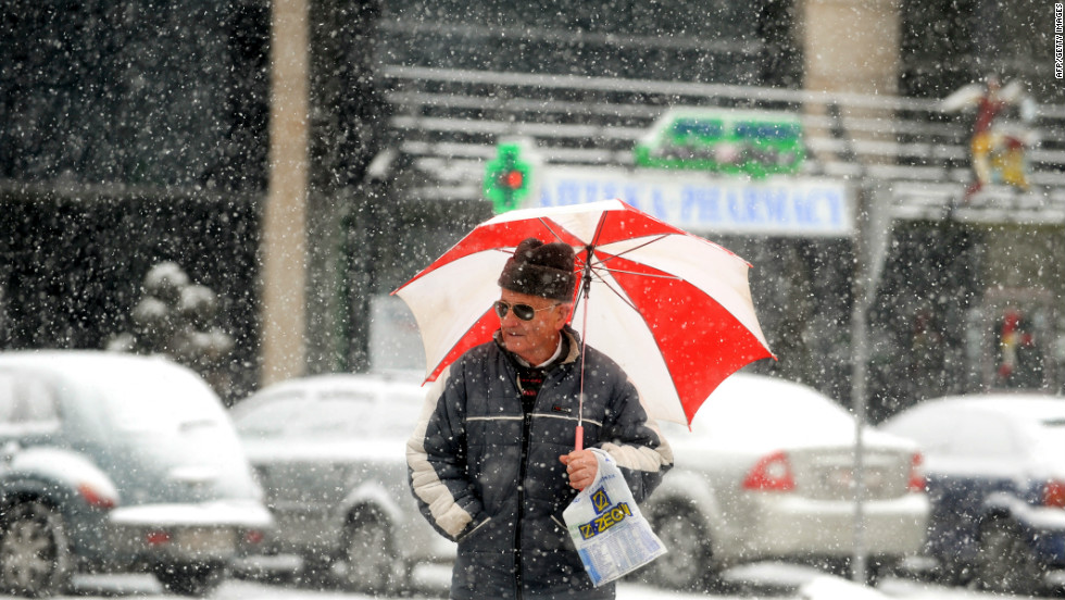 A man walks under an umbrella during a snowfall in downtown Skopje on February 6, 2012.