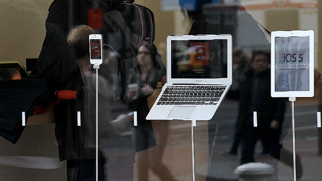 A Macbook Air laptop, an iPad 2 and an iPhone sit on display in a store window.