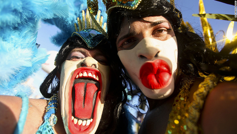 Brazilian revelers pose for photographers during carnival celebrations along Ipanema Beach on Saturday  in Rio de Janiero. Carnival revelers descended on Rio, flocking to hundreds of block parties and cramming into designated areas to watch elaborate parades from dusk until dawn. This year, about 850,000 tourists visited Rio for carnival celebrations, according to tourism officials.