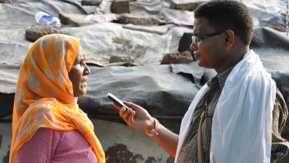 A woman is interviewed in a Delhi slum by a CGNet Swara citizen journalist.