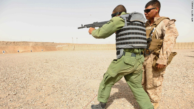An Afghan police trainee practices shooting as a U.S. Marine looks on at Adraskan Police Training Center on July 15, 2011.