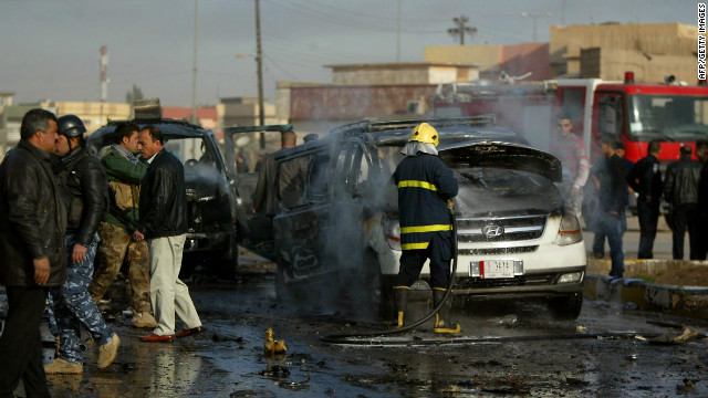 An Iraqi firefighter douses a car as security forces inspect the site of a blast in the northern city of Kirkuk on February 23, 2012.