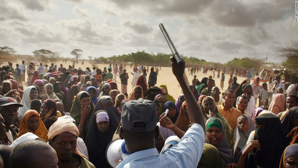 A security officer keeps order in Dadaab as hundreds of desperate people try to move to a less crowded refugee camp set up three days' drive away.