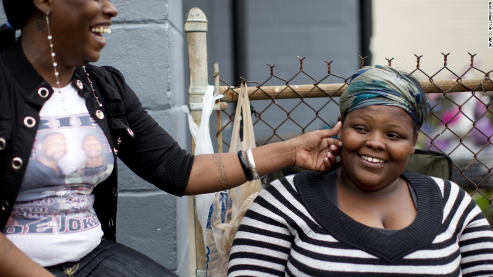 """Trina Bordley wears a shirt memorializing Joseph """"Joker"""" Elliott, the 17-year-old killed during an argument at his home. She pinches Timeshika Beasley's cheek as they sit outside in the Zion City neighborhood."""