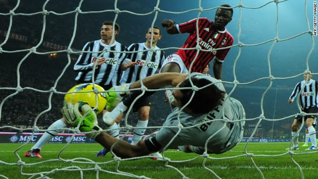 Juventus goalkeeper Gianluigi Buffon claws back a goalbound header from  AC Milan midfielder Sulley Ali Muntari.