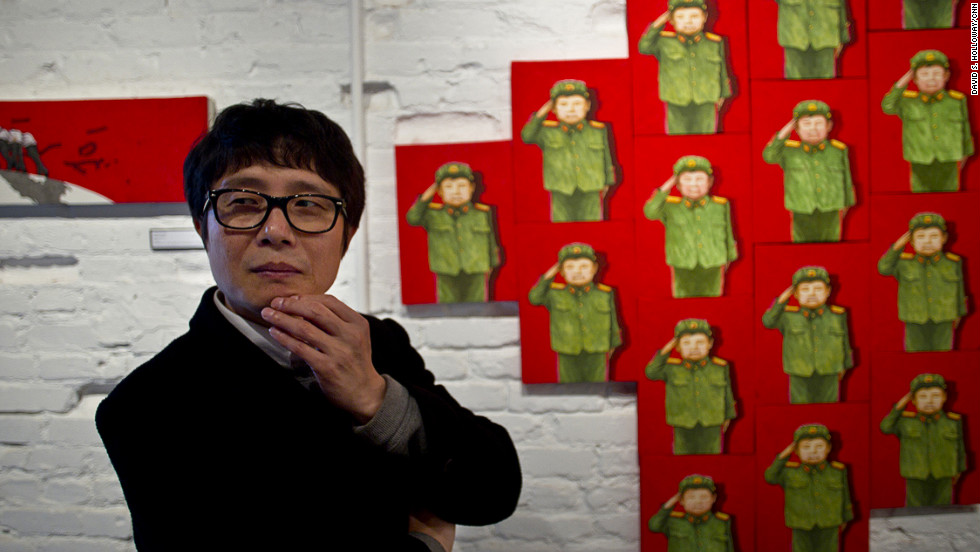 "Song Byeok's paintings are often about coming to terms with life outside North Korea. Behind him is the painting ""Child Warrior,"" depicting the curious North Korean custom of dressing children in military clothes on special birthdays. Song painted the boy with his eyes closed."