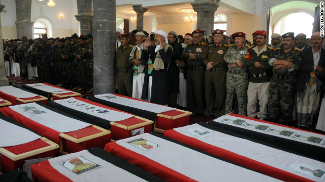 Yemenis pray over the coffins of troops killed when a suicide bomber blew up a vehicle outside a presidential palace in Mukalla on February 27, 2012.
