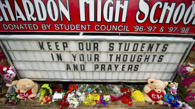 Flowers adorn the sign outside Chardon High School in Chardon, Ohio, after three students were killed in a shooting rampage.