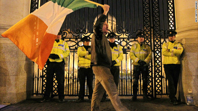 A protester waves an Irish flag outside the Irish Prime Ministers office in Dublin, Ireland, on November 21, 2010.