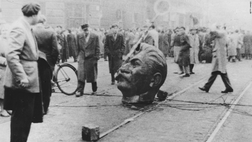 Protesters mill around a decapitated statue head of former Soviet leader Joseph Stalin on the streets of the Hungarian capital Budapest.