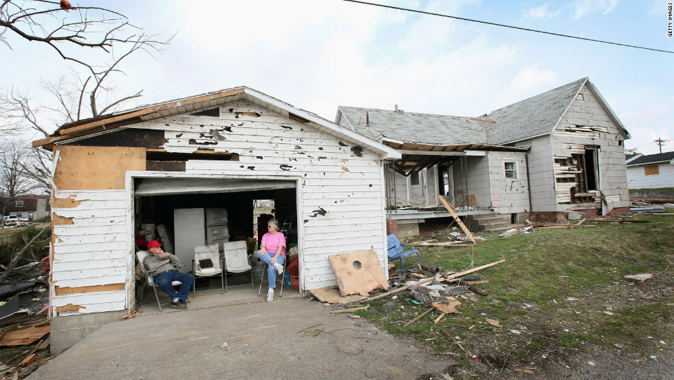 Dale Barnfield, left, and his niece Linda Mayberry wait for an insurance adjuster outside Barnfield's tornado-damaged home in Harrisburg.