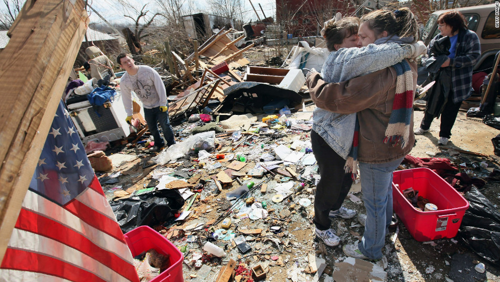 Melody Zollman, left, gets a hug from her sister Michelle Browning as they stand among the remains of Zollman's home in Henryville after it was destroyed by a tornado on Friday.