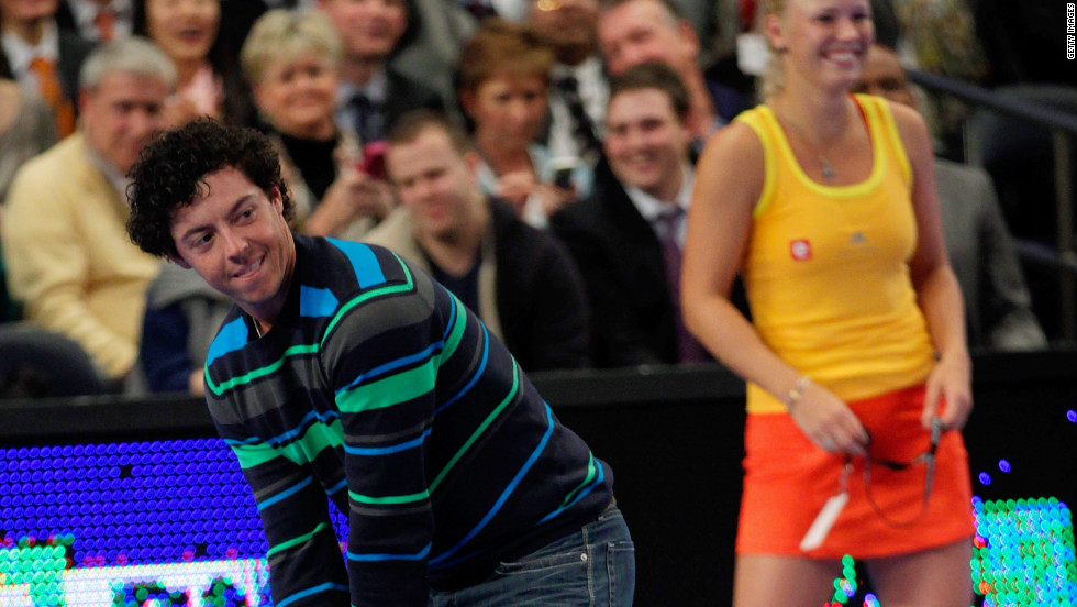 Wrong sport Rory ! McIlroy addresses a tennis ball golf style with Maria Sharapova at the other end.