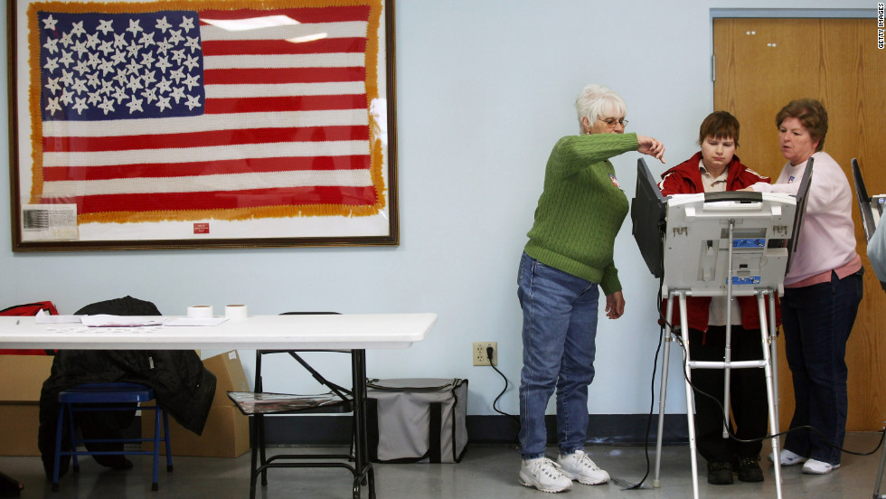 Poll workers assist a voter at a polling place during Super Tuesday voting in Carrollton, Ohio.