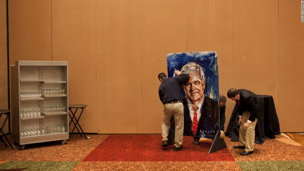Workers set up a painting of Newt Gingrich by artist Steve Penley before a rally in Atlanta on Tuesday.