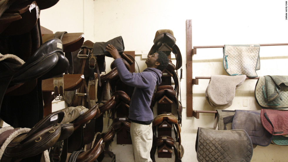 "Kenshaun Walker grabs a saddle to put on a horse before heading out ride. ""This is my second home, and I need to be here if I want to be something in life,"" said Walker, 15, who plays on the men's team and is in his sixth year with the program. ""This is my top way to get me out of Philadelphia, out of all the people who's making bad decisions."""