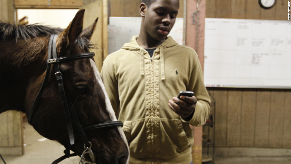"Sixteen-year-old Brandon Rease checks his cell phone while waiting for the others to finish tacking their horses. Rease, had to walk several blocks in the rain from the bus stop to reach the stable. ""In my neighborhood and all of our neighborhoods, there's normal day-to-day violence, drug dealing and kids around a bunch of negativity. When you come to the barn or travel, all of that is washed away and you can be a kid."""