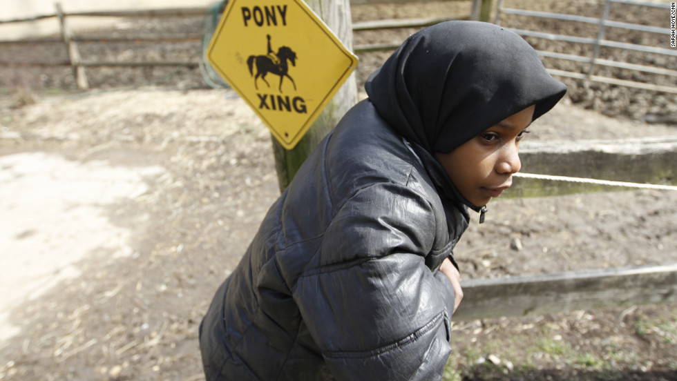 "Sudayaah Myers, 9, dangles from the paddock fencepost. Lezlie Hiner, who opened the barn doors in 1994, founded Work To Ride. In addition to working with the horses, staff and volunteers provide after school tutoring and require students maintain passing grades. ""I fell off a pony before, but I got back on it,"" she said. ""We all have our favorites."""