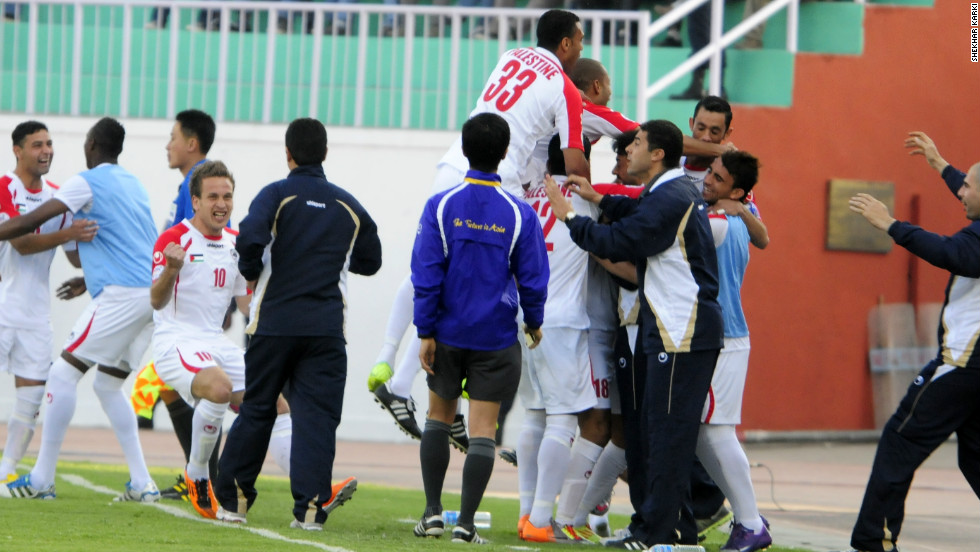 The Palestinian team celebrate their first goal against Nepal with members of the coaching staff on the touchline. Palestine won the match 2-0.