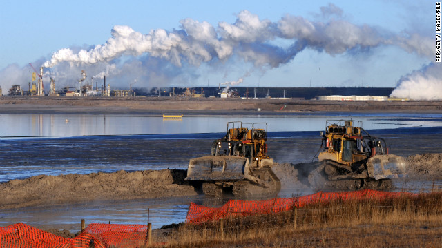 Workers use heavy machinery in the tailings pond at an oil sands extraction facility near Fort McMurray, Canada.