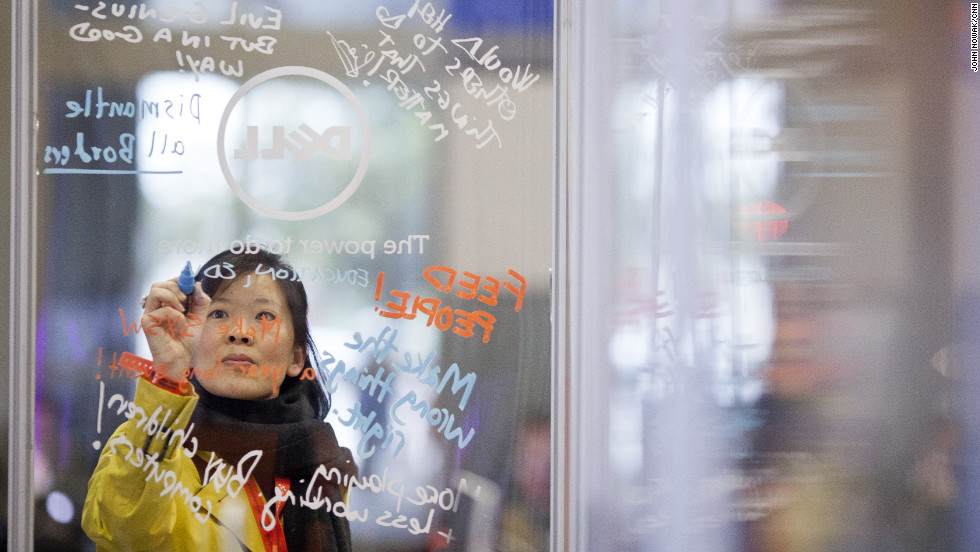 An attendee scrawls a message on a transparent board.
