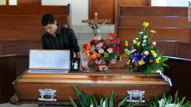 A young man stands beside the coffin of Honduran journalist Saira Fabiola Almendarez, murdered on March 2, 2012.