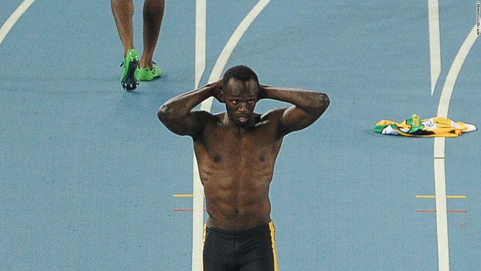 Blake's compatriot Usain Bolt was favorite to add the title to his 100m and 200m Olympic crowns, but he was disqualified for a false start. In the background, Blake walks back to the blocks.