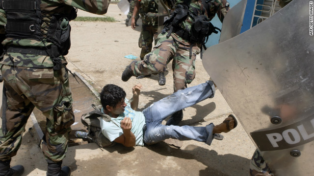 A gold miner clashes with Peruvian riot policemen during protests in the country's Madre de Dios region on March 14, 2012.
