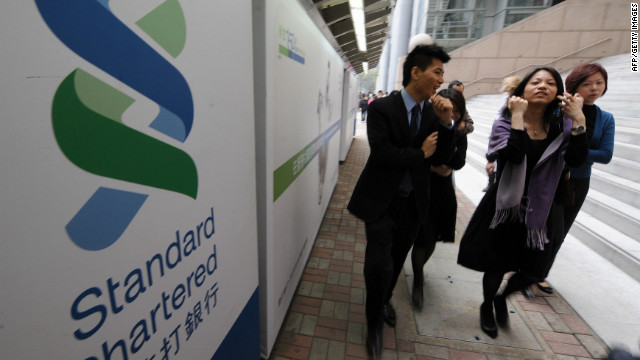 People walk past the Hong Kong headquarters of Standard Chartered bank on March 3, 2009.