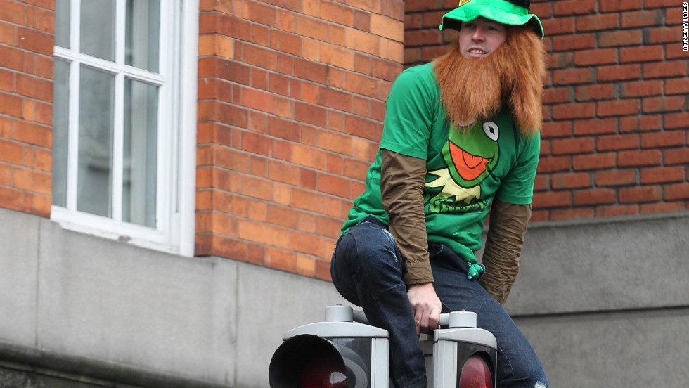 A man watches the parade from atop a traffic light. In Ireland, St. Patrick's Day is a national holiday with banks, stores and businesses closing for the day. It is tradition for people to wear green clothing on the holiday.