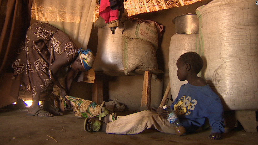 Grace Lagat ties up her seven-year-old son Thomas, who suffers from Nodding Disease, so he can't wander off when she tends to her field or is out of the homestead in Northern Uganda where more than 3,000 kids have the syndrome.