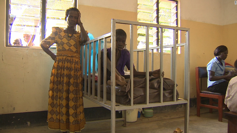 A sufferer of Nodding Disease is put in a child's crib at Antanga Health Center, Uganda, so that he doesn't injure himself. The affliction is associated with violent epilepsy-like convulsions that can lead to permanent disabilities.