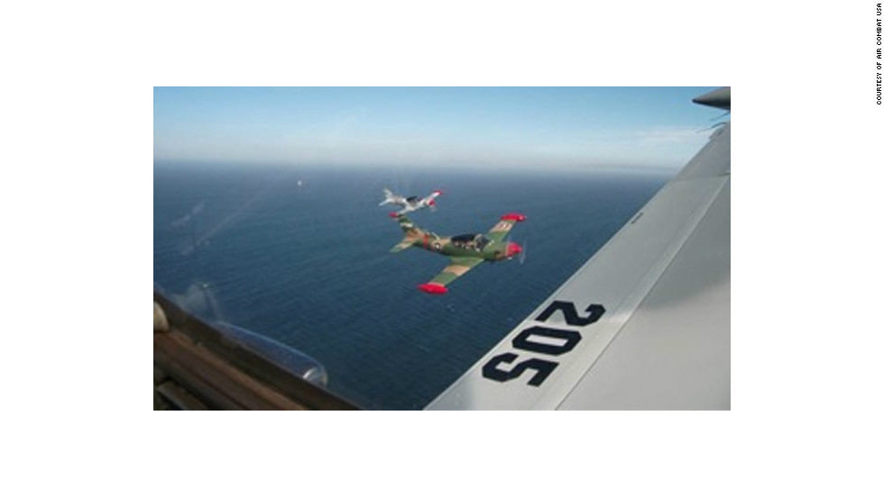 "The view from the cockpit of a SIAI-Marchetti fighter plane ahead of an ""executive dogfight."""