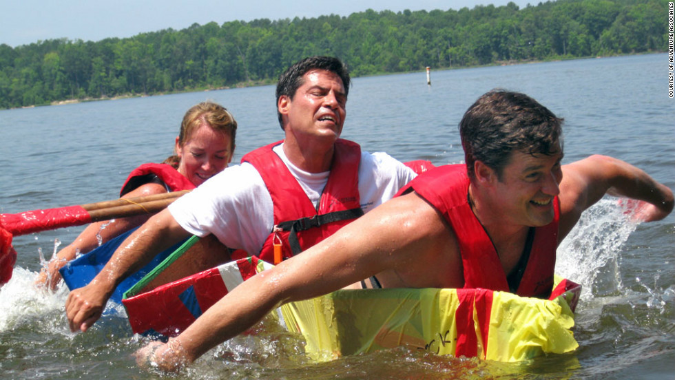 Executive participants strain to stay afloat as they attempt to cross a lake in a vessel they have built on an Adventure Associates retreat in North Carolina, USA.