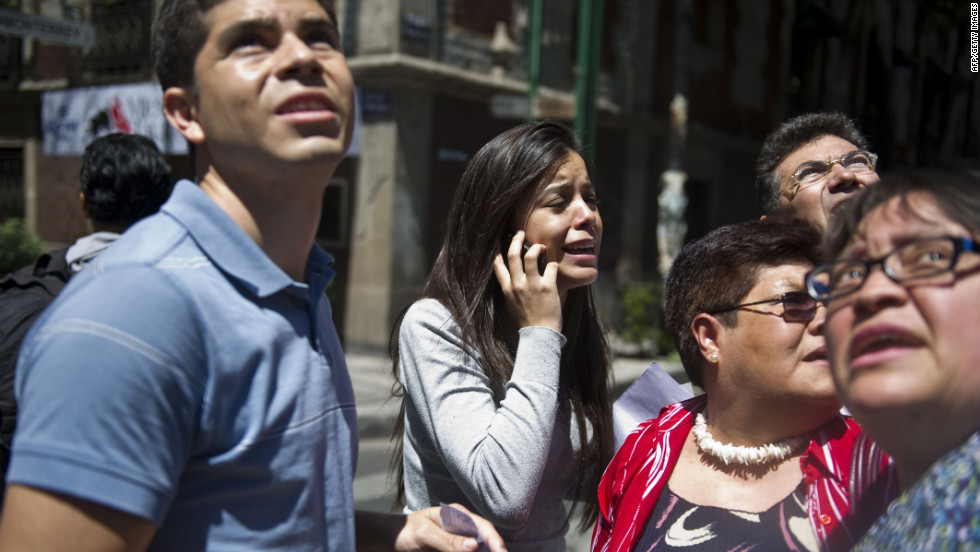 A woman cries on the phone as people move to safety in Mexico City.