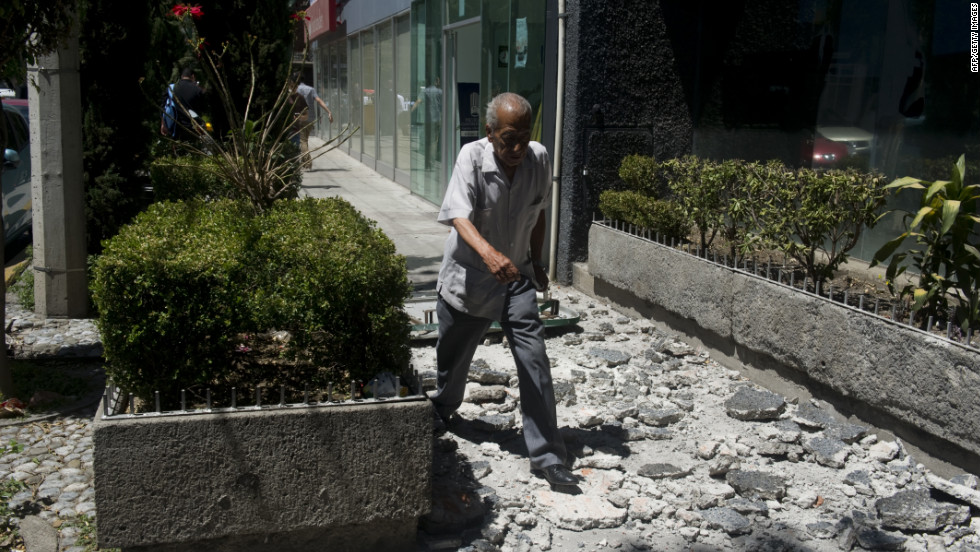 A man walks over debris from a building in Mexico City.