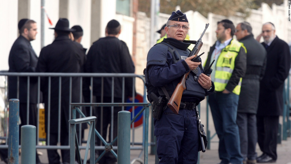 A policeman stands guard on Tuesday in front of the Jewish school where four people were killed the day before in Toulouse.