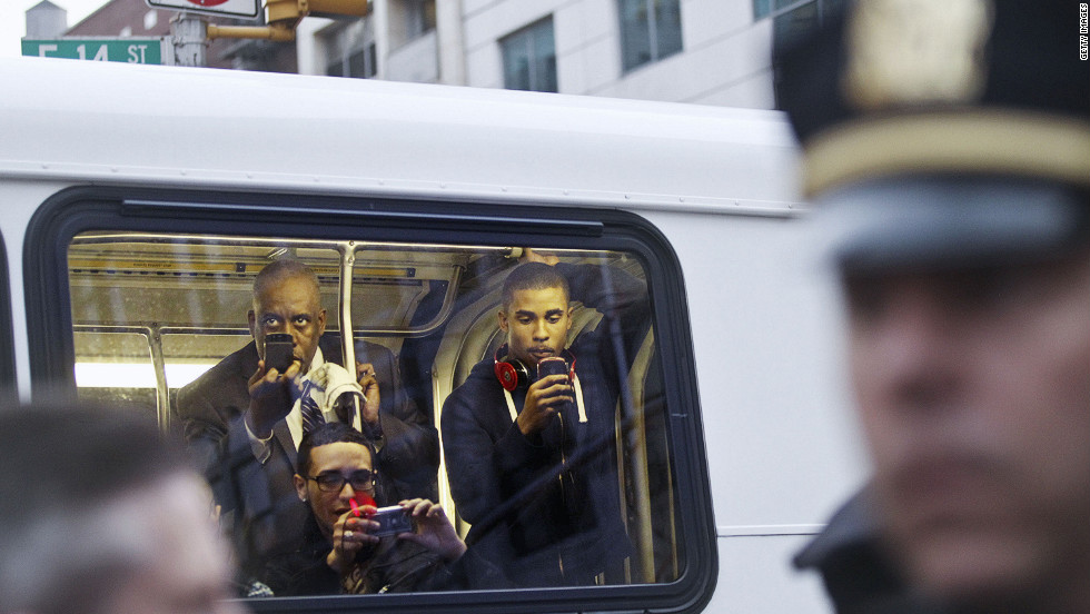 Passengers on a bus take photos of the demonstrators.