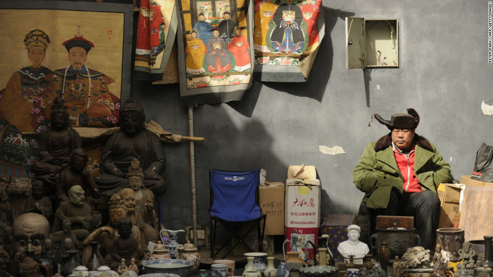 A vendor waits for customers at Panjiayuan antique market, where you can buy anything from Ming Dynasty pottery to souvenirs from the Cultural Revolution.