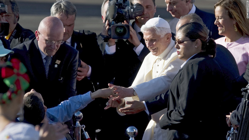 The pope greets a child upon his arrival at the Guanajuato airport.