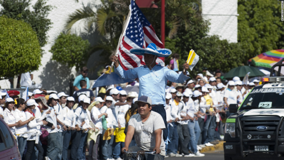 A man waves national flags of the United States and Vatican City as young people wait on the sidewalk for the arrival of the pope along Lopez Mateos Boulevard.