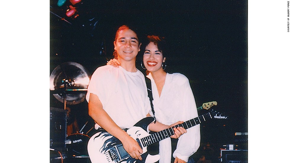 "Selena and her husband Chris onstage with his ""Selena"" guitar. ""The next time we played in Austin, Tony bought back my guitar with this gorgeous picture of Selena on it...Selena covered her mouth and her eyes went wide. She was all smiles and totally tripping. 'I can't believe you did that for me!'"" -- excerpt from ""To Selena with Love,"" by Chris Perez."
