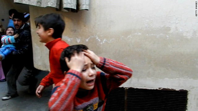 A man runs carrying a toddler as children weep during fighting in the Bab Tudmor neighborhood of the city of Homs in February