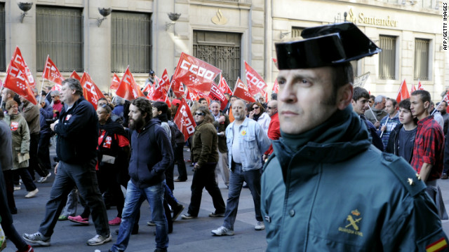 "A ""Guardia Civil"" police officer walks along demonstrators during a day of national strike in central Madrid, Spain, on March 29."