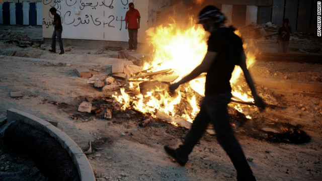 A Bahraini Shiite Muslim walks past a fire as protestors clashed with riot police on March 31, 2012.