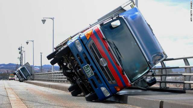A typhoon-like storm sweeps two trucks over on a bridge at Toyama, western Japan on April 3, 2012.