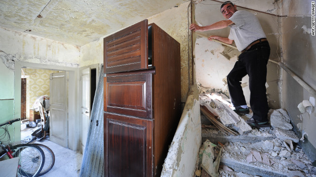 A L'Aquila resident in his damaged home.